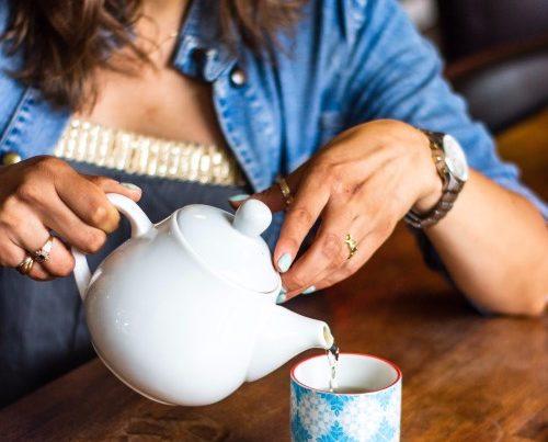 mulher serve chá em um pequeno copo de cerâmica