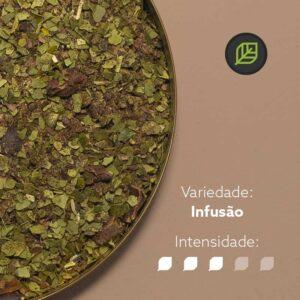 Chá mate matequero em recipiente metálico na metade esquerda da imagem. Fundo marrom claro. Símbolo do mate in box no canto superior direito. Em escrito: Variedade - Infusão. Intensidade nível 3 de 5.