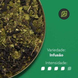 Chá mate matequero em recipiente metálico na metade esquerda da imagem. Fundo verde. Símbolo do mate in box no canto superior direito. Em escrito: Variedade - Infusão. Intensidade nível 4 de 5.