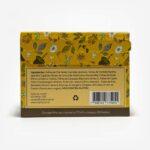 Pacote tcháfino amarelo de costas. Fundo cinza claro. Pacote amarelo com ilustrações de flores e chimarrão. Em escrito: Ingredientes: Chá verde, hortelã, camomila, boldo, carqueja, capim cidró, laranja, anis estrelado, gengibre e funcho.