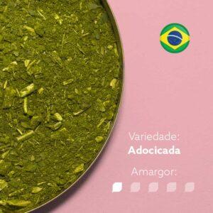 Erva-mate em recipiente metálico em detalhe com fundo rosa. Bandeira brasileira redonda no canto superior direito. Em escrito: Variedade - Adocicada. Amargor 1 de 5 níveis.