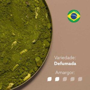 Foto em plano de um recipiente metálico com Erva-mate Meta Mate Defumada. Fundo marrom claro com bandeira do brasil circular no canto superior direito. Em escrito: Variedade - Defumada. Amargor nível 2 de 5.