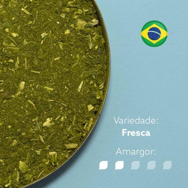 Erva-mate Moída Grossa em recipiente metálico e fundo em azul claro. Bandeira do Brasil circular no canto superior direito. Em escrito: Variedade - Fresca. Amargor nível 2 de 5.
