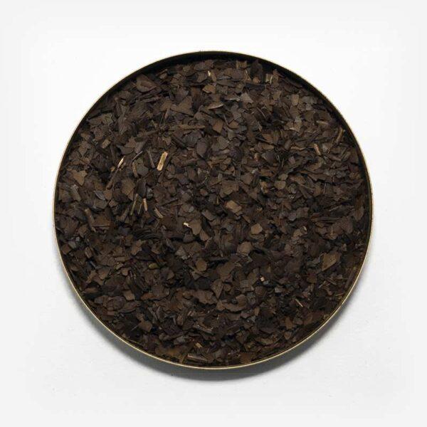 Blend Samba de erva-mate tostada em recipiente metálico no centro da imagem. Fundo cinza claro. Erva-mate tostada com presença de pouco palito. Erva-mate escura, cozida. Erva-mate para chá mate.