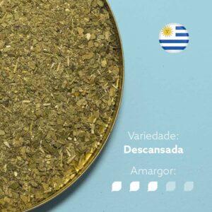 Erva-mate Padrão Uruguaio em recipiente metálico na metade esquerda da imagem. Bandeira circular do uruguai no canto superior direito. Em escrito: Variedade descansada. Amargor nível 3 de 5.