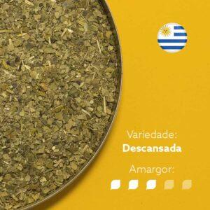 Erva-mate Canarias em recipiente metálico ocupando metade esquerda da imagem. Fundo laranja. Bandeira circular do uruguai no canto superior direito. Em escrito: Variedade Descansada. Amargor nível 3 de 5.