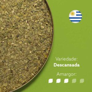 Erva-mate Baldo em recipiente metálico ocupando metade esquerda da imagem. Fundo verde claro . Bandeira circular do uruguai no canto superior direito. Em escrito: Variedade Descansada. Amargor nível 3 de 5.