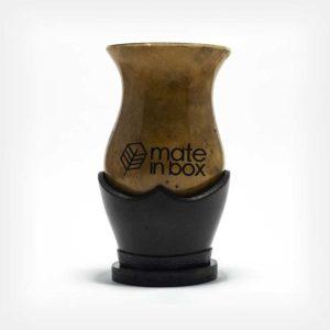 Cuia de Porongo Mate in Box com logo no centro em fundo cinza claro. Cuia sem pé fixo, com suporte em couro legítimo. Logo marcada por laser.