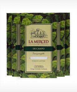 Pacotes de La Merced de Campo 500 gramas com folhas de erva-mate verde desenhada por todo ele. Em escrito La Merced em vermelho e De campo em fundo verde escuro.