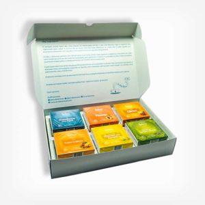Caixa de Chás aberta, mostrando 6 caixas de sabores de chá. São eles: Aromatizante para água, Frutas Tropicais, Pêssego, Abacaxi com Hortelã, Cítrico e Chá verde com Hortelã e Alecrim. Cada caixinha dentro do Tea Box tem 10 sachês de cada sabor.