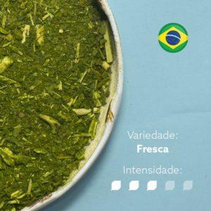 Erva-mate Morandi Moída Grossa em recipiente metálico ocupando metade esquerda da imagem. Fundo azul claro e bandeira do Brasil circular no canto superior direito. Em escrito: Varidade composta com intensidade nível 3 de 5.