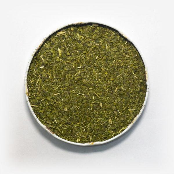Blend de erva-mate Grunge em recipiente metálico no centro. Fundo cinza claro. Erva-mate verde defumada. Pouca presença de palitos. Palitos muito triturados. Erva-mate verde fresca, parecida com padrão brasileiro.