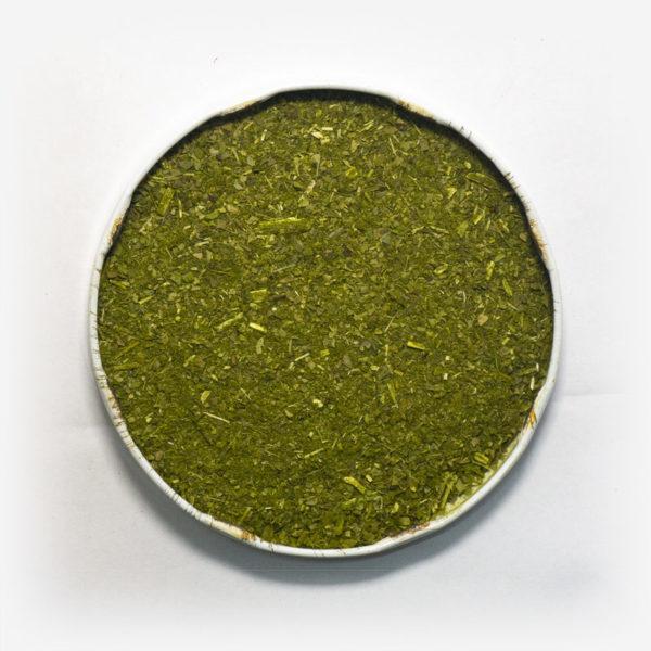 Blend de erva-mate POP em recipiente metálico no centro. Fundo cinza claro. Erva-mate verde e fresca. Erva-mate fina. Pouca presença de palitos. Palitos muito triturados. Erva-mate verde fresca.