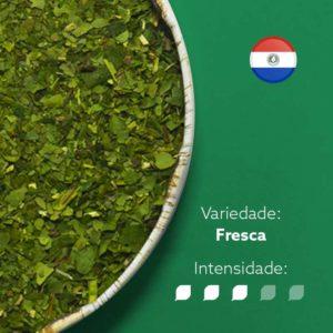Erva-mate Castelhana Premium pura folha em recipiente metálico ocupando metade esquerda da imagem. Fundo verde escuro e bandeira do Paraguai circular no canto superior direito. Em escrito: Variedade Fresca com intensidade nível 3 de 5.