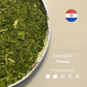 Erva-mate Morandi em recipiente metálico ocupando metade esquerda da imagem. Fundo marrom claro e bandeira do Paraguai circular no canto superior direito. Em escrito: Variedade - fresca. Intensidade nível 2 de 5.