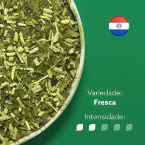 Erva-mate Castelhana pura folha em recipiente metálico ocupando metade esquerda da imagem. Fundo verde escuro e bandeira do Paraguai circular no canto superior direito. Em escrito: Varidade fresca com intensidade nível 2 de 5.