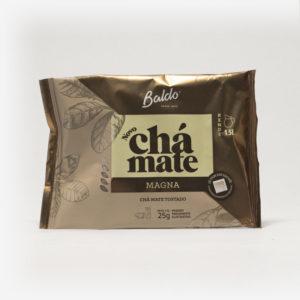 Pacote de chá mate magna em fundo cinza claro. Pacote com tons de marrom. Detalhes escuros no canto superior direito, formando um triângulo. Em escrito: Baldo, novo chá mate magna. Chá mate tostado. 25 gramas.