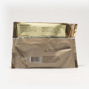 Pacote de chá mate magna em fundo cinza claro de costas. Pacote com tons de marrom. Modo de preparo disponível na descrição do produto.