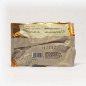 Pacote de chá mate magna em fundo cinza claro de costas. Pacote com tons de marrom com laranja. Modo de preparo disponível na descrição do produto.
