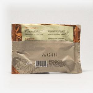 Pacote de chá mate magna em fundo cinza claro de costas. Pacote com tons de marrom com laranja escuro. Modo de preparo disponível na descrição do produto.