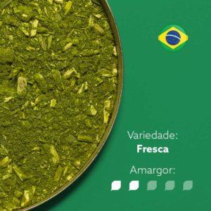 Erva-mate Querencia Amada em recipiente metálico ocupando metade esquerda da imagem. Fundo verde e bandeira do Brasil circular no canto superior direito. Em escrito: Varidade fresca com amargor nível 2 de 5.